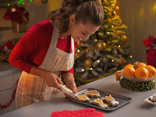 Happy young housewife decorating christmas cookies with glaze