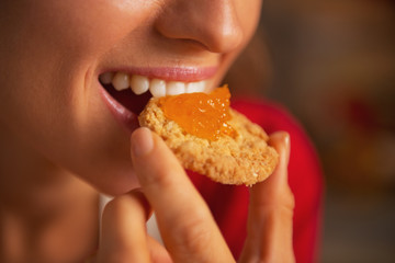 Portrait of young woman eating cookie with orange jam