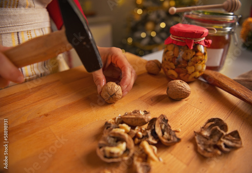 Closeup on young housewife chopping walnuts