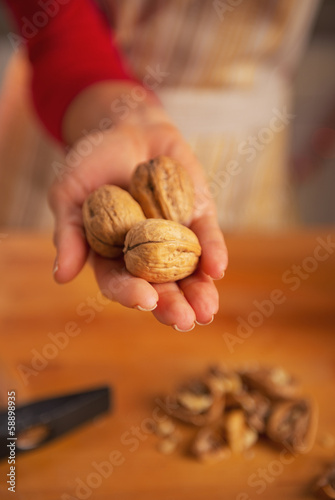 Closeup on young housewife showing walnuts
