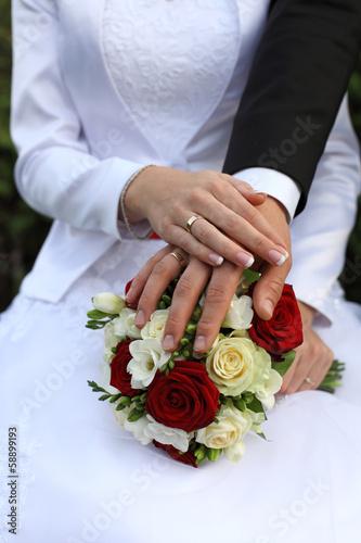Dłonie młodej pary, obrączki i ślubny bukiet kwiatów.