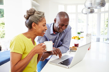 Mature African American Couple Using Laptop At Breakfast