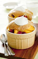 Closeup of two berry peach cobblers in ramekins.