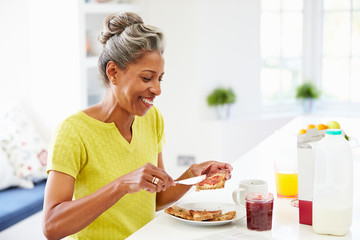 Mature Woman Eating Breakfast Spreading Jam On Toast