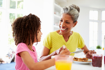 Grandmother And Granddaughter Having Breakfast Together