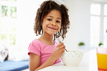 Young Girl Having Breakfast In Kitchen