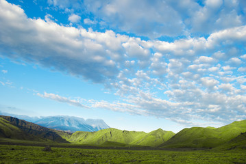 landscape of green meadow, mountain, blue sky and clouds, Russia