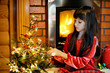 Child girl by a fireplace on Christmas