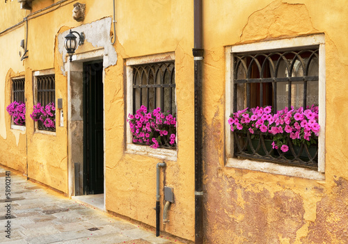 Picturesque yellow building with pink flowers.