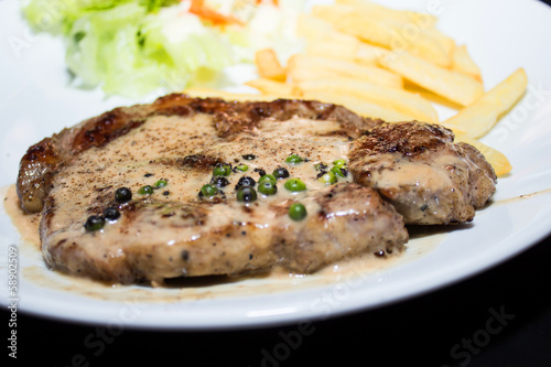 Beef steak with black pepper sauce on a white plate