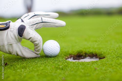 Golf player man pushing golf ball into the hole