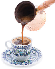 Pouring Turkish coffee in cup isolated on white background