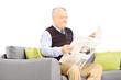 Senior gentleman seated on a modern sofa reading a newspaper