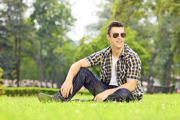 Handsome guy with sunglasses sitting on grass