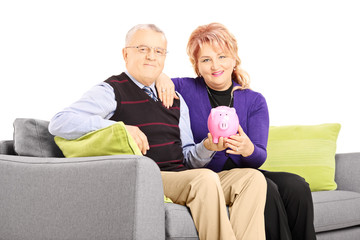 Mature couple sitting on a sofa and holding a piggy bank