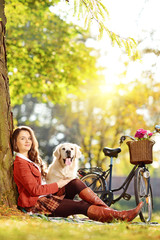 Pretty female sitting on a grass with her dog and looking at cam