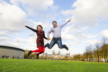 Outdoor happy couple jumping in Museumplein, Amsterdam