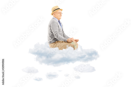 Senior man with hat seated on clouds meditating