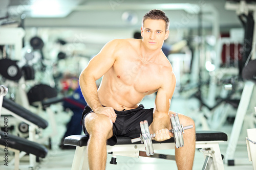 Shirtless muscular man lifting weight in a fitness club