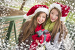 Two Happy Teens Wearing Santa Hats Holding a Wrapped Gift
