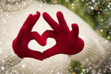 Woman Wearing Red Mittens Holding Out a Heart Hand Sign