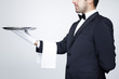 Professional waiter holding an empty silver tray over gray backg