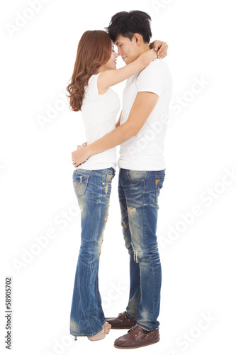 full length happy couple hugging and looking