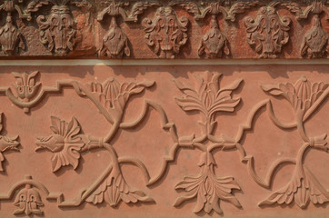 Wall of Taj Mahal with intricate patterns in red sand stone