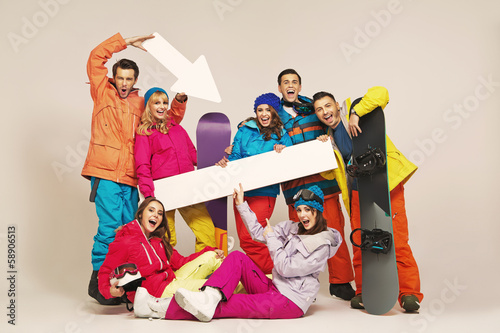 Cheerful snowboarders with fancy signs