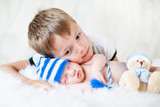 child boy embracing at sleeping newborn baby brother