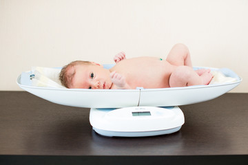 newborn baby on weighing scale