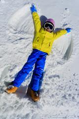 Winter fun - Snow Angel -  skier girl playing in snow