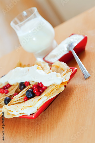 pancakes with berries and glass of milk