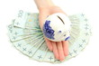 Piggy bank on hand of woman and banknotes. White background