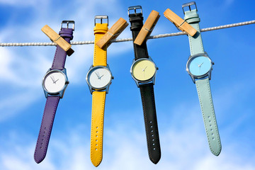 composition of colourful watches on blue sky background
