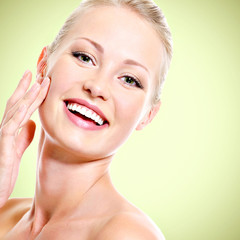 Portrait of healthy smiling woman touching face