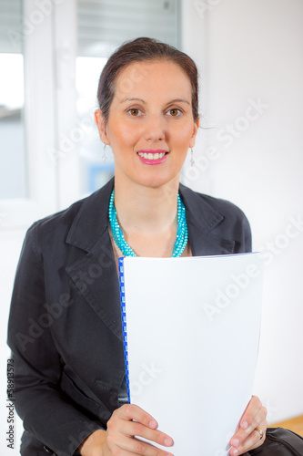 Portrait of a businesswoman with lots of paperwork at office