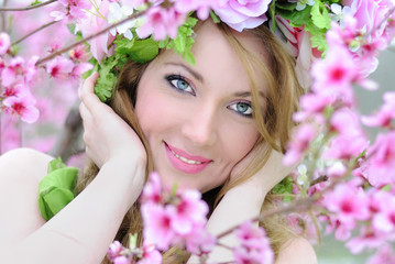 Beautiful girl in a flowered garden peach