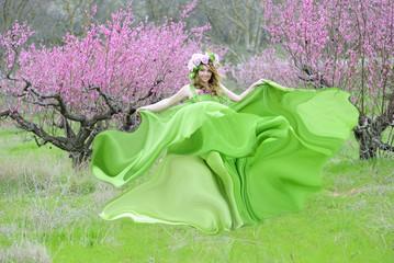 Beautiful girl in a flowered garden peach
