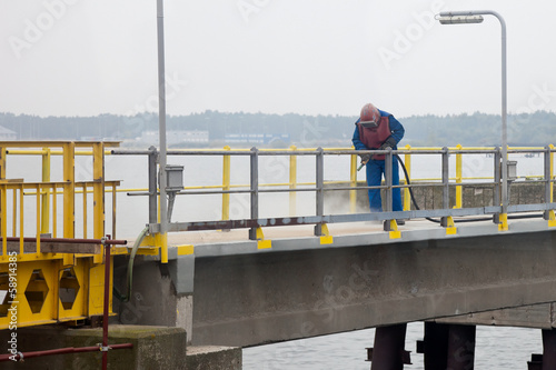 Worker sandblasting barrier on the waterfront. - 58914385