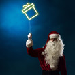 Santa holding a light symbol of the Christmas box