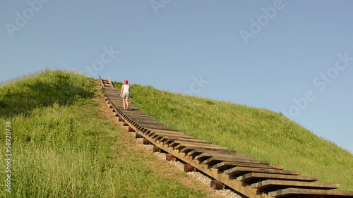 tourist woman climb wood stair on hill on background of blue sky