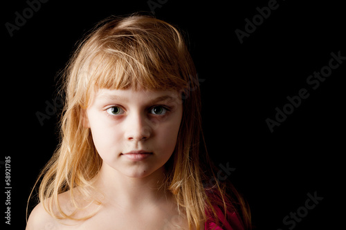 Closeup studio portrait of blond Caucasian little girl on black
