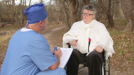 Male doctor talking with senior patient in wheelchair