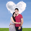 Smiling couple with clouds shaped of heart