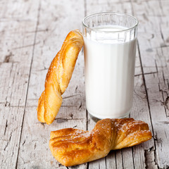 glass of milk and two fresh baked buns