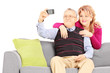Man and woman on a sofa taking pictures of themselves with phone