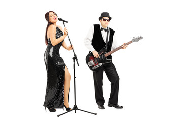 Man playing a bass guitar and woman singing