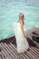 The bride on a wooden platform over the sea,with a retro effect