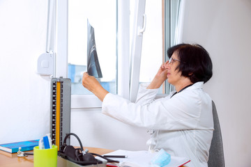 senior woman doctor in office looking at x-ray